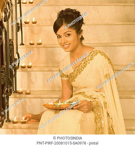 Woman placing oil lamp on a staircase and smiling
