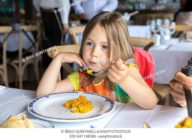 portrait of four years old blonde cute girl blowing rice on fork to cool eating Spanish paella in restaurant