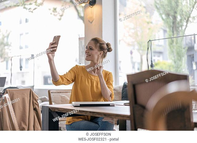 Young woman sitting in coworking space, taking smartphone selfie