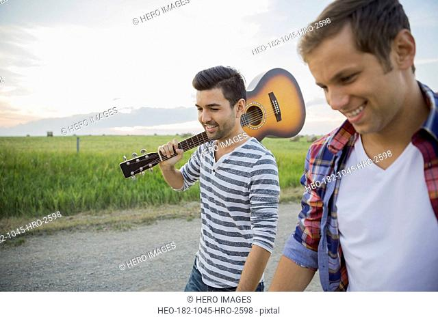 Young men with guitar walking on country road