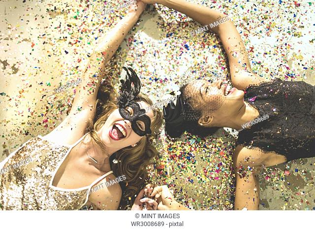 Two young women lying on a carpet surrounded by fallen confetti