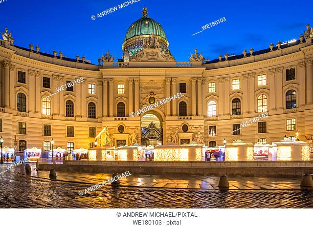 Hofburg, the imperial palace of the Habsburgs, from Michaelerplatz with a Christmas market, at dusk, Vienna, Austria