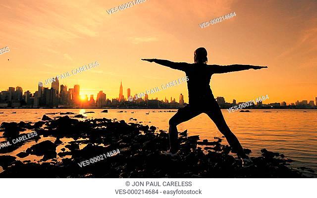 Silhouette eines Menschen, der bei Sonnenuntergang Yoga?bungen macht. Im Vordergrund Wasser, im Hintergrund eine Stadt