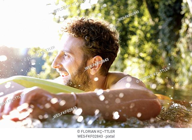 Happy young man with surfboard in a lake