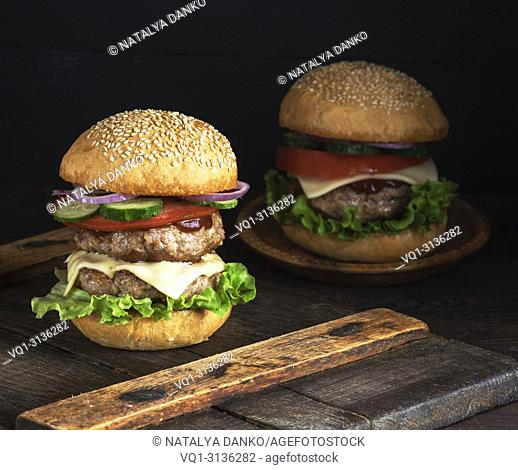 large burger with two fried cutlets, cheese and vegetables in a round wheat flour bun