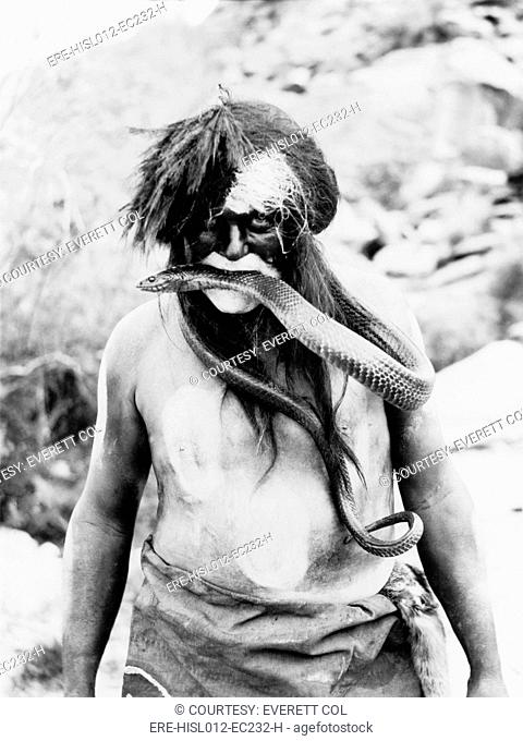 Hopi Indian with painted face and body and snake in mouth. Photo by Ralph Murphy, 1924
