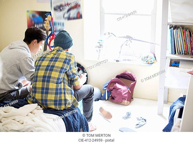 Two teenage boys sitting on bed in messy room