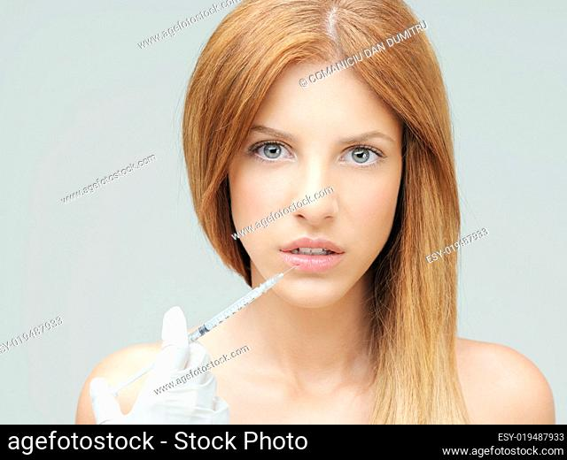 young woman doctor hands injecting colagen lips