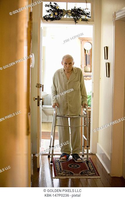 Feeble senior man walking down hallway using walker