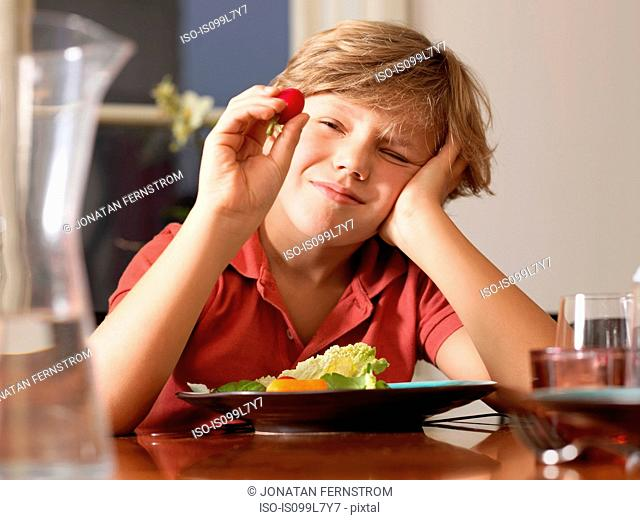 Boy looking closely at radish at table
