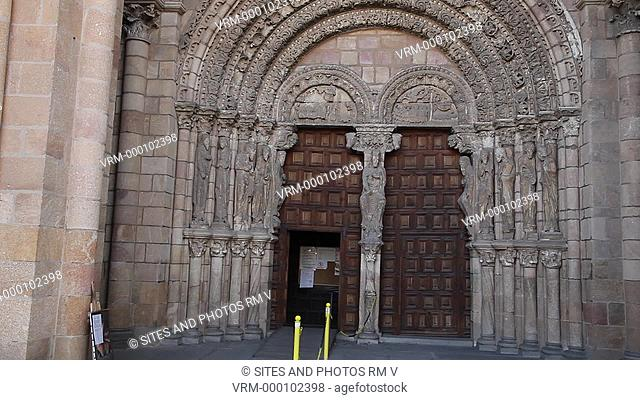 Tilt up. Daylight. Exterior: Romanesque carvings of the central portal. The Romanesque basilica was erected between the 11th and 14th centuries