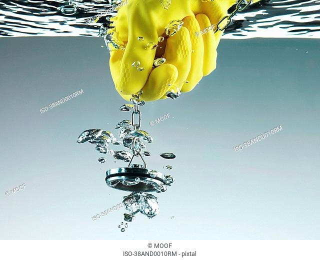 Rubber glove pulling plug in water