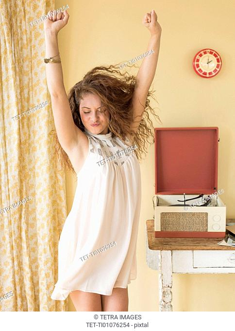 Portrait of woman dancing happily in room