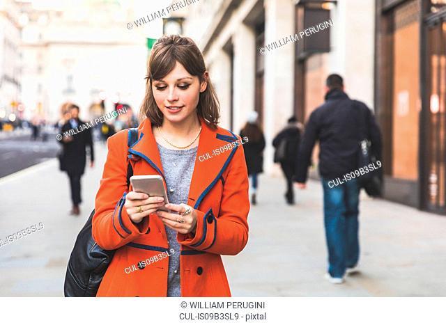 Young woman walking along street using smartphone