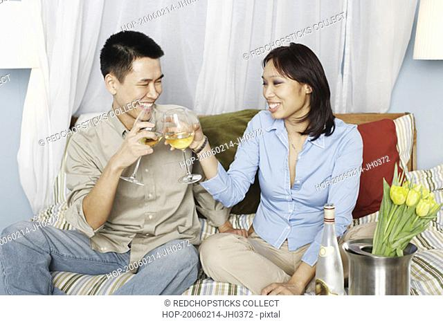 Young couple sitting on the bed toasting with wineglasses