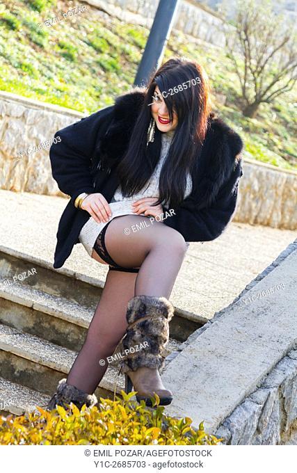 Teen girl adjusting Black stocking under short dress smiling at camera