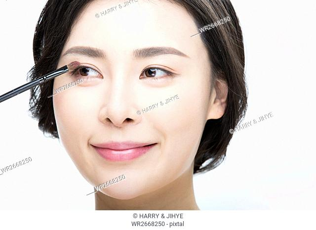 Portrait of young smiling woman with eyeshadow brush
