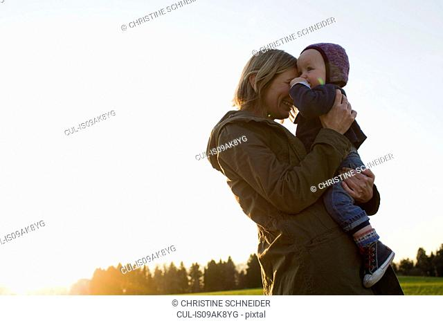 Mature mother and baby daughter in field at sunset