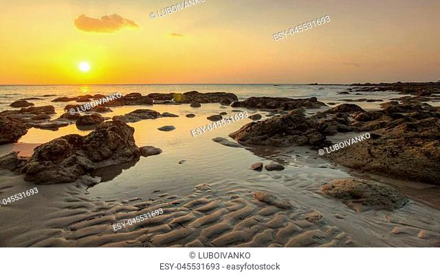 Beach in golden sunset light during low tide showing sand formations and rocks not covered by the sea. Kantiang Bay, Ko Lanta, Thailand