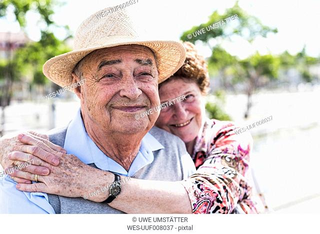 Portrait of happy senior with his smiling wife in the background