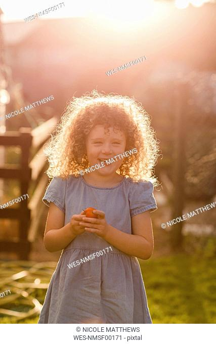 Portrait of little girl standing at backlight in the garden