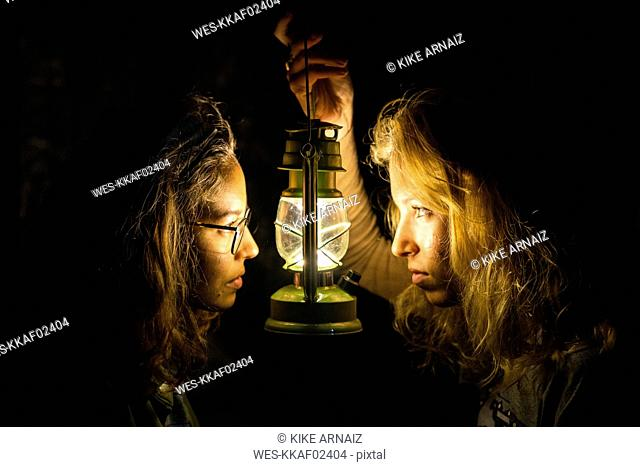 Two young women with storm lantern in the dark facing each other