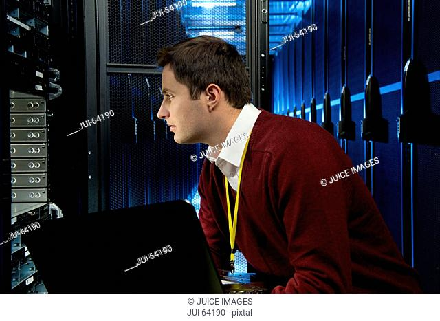 Technician checking server in storage cabinet