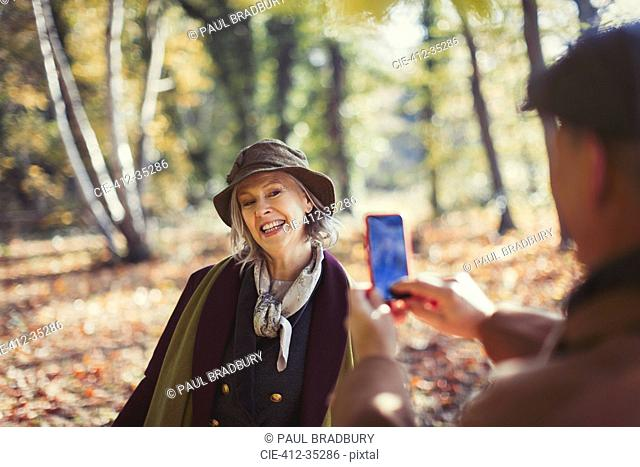 Playful senior woman being photographed by husband with camera phone in autumn park