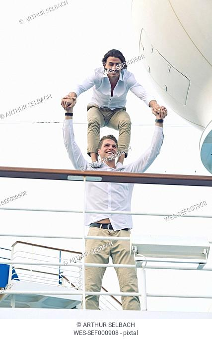 Two young men messing about on cruise ship, balancing on shoulders