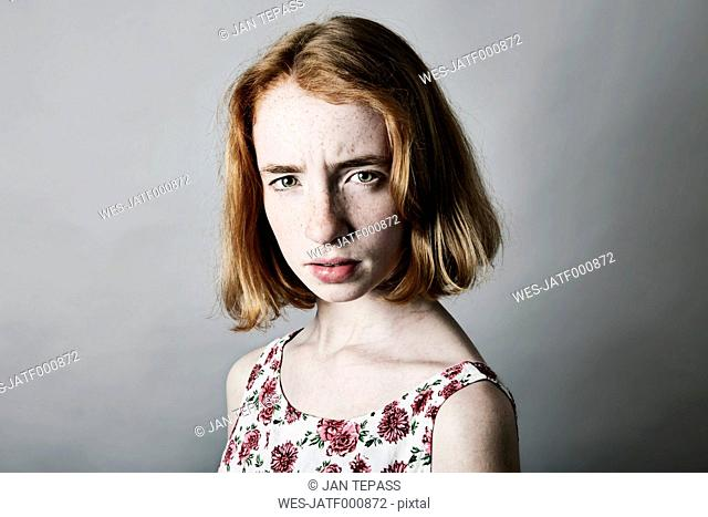 Portrait of angry girl in front of grey background
