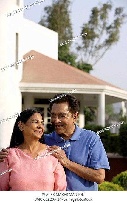 smiling couple standing in front of house