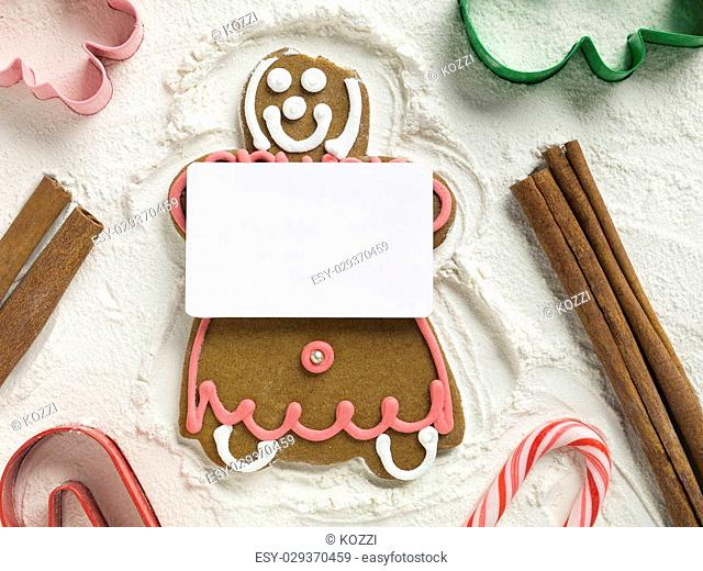 Gingerbread girl holding an empty white card