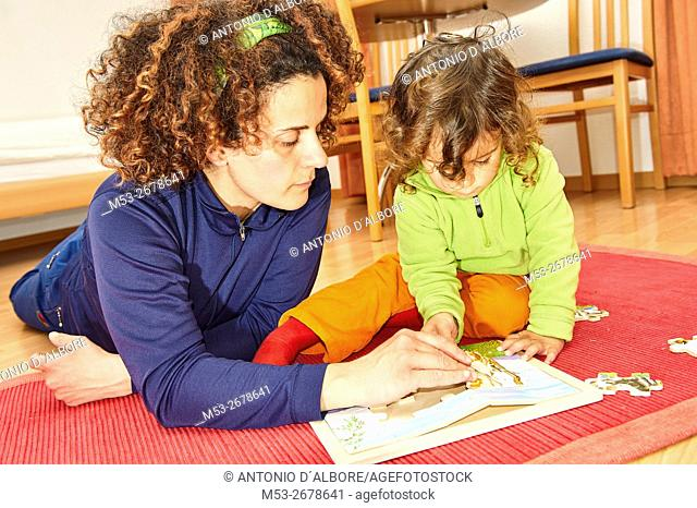 A two years old baby girl making a wooden puzzle assistend by her mother