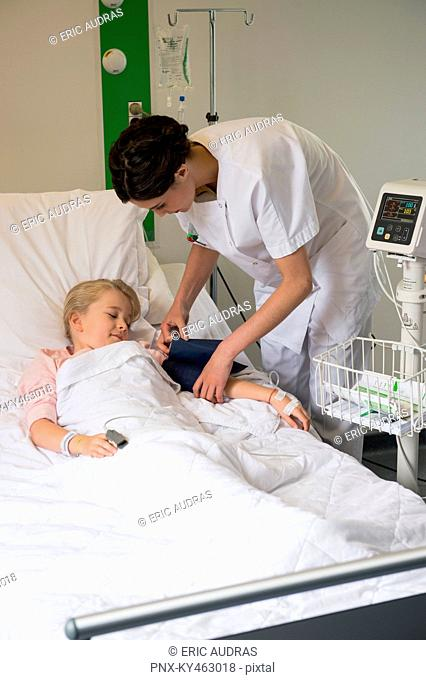 Medical attendant examining blood pressure of a girl patient in hospital bed
