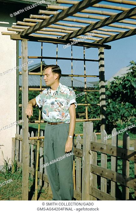 Missionary in Japan, side view, standing with his arm leaning against a bamboo arbor, picket fence visible behind the man, his eyes closed