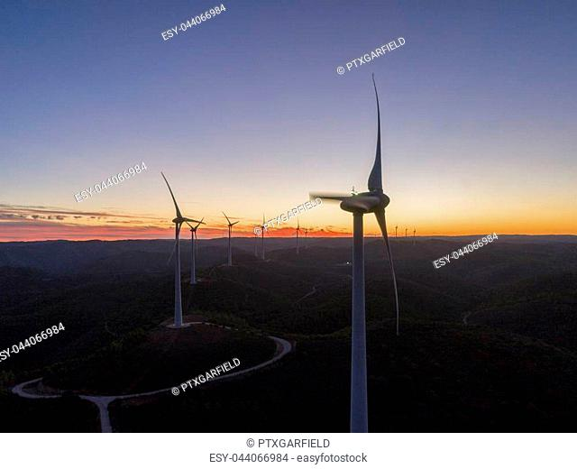 Aerial panoramic Wind farm turbines silhouette at sunset. Clean renewable energy power generating windmills. Algarve countryside. Portugal