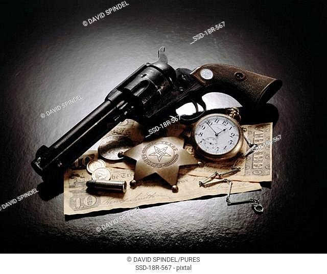 Close-up of an antique handgun with a badge, pocket watch and bullets