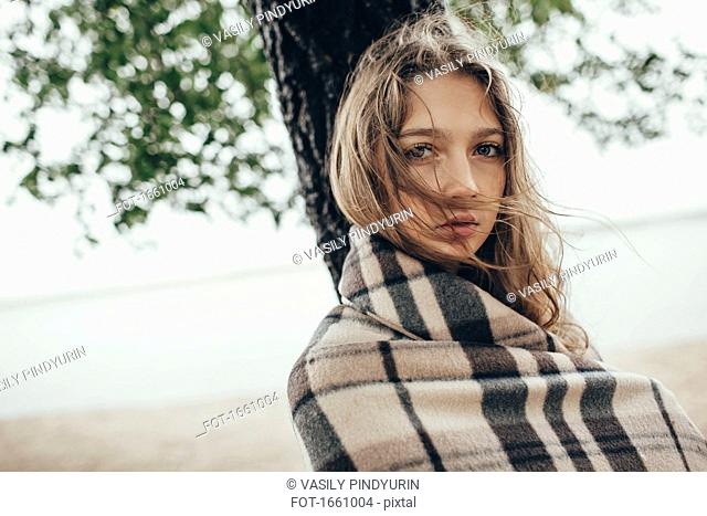 Portrait of teenage girl wrapped in blanket against lake on windy day