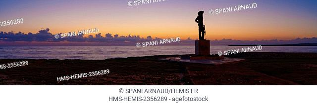 Cuba, Holguin, Gibara, Panorama of the beach at sunset with silhouette of a statue to the glory of the revolution