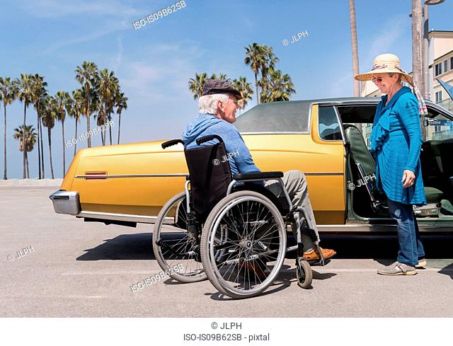 Senior woman chatting to husband in wheelchair by vintage car at Venice Beach, California, USA