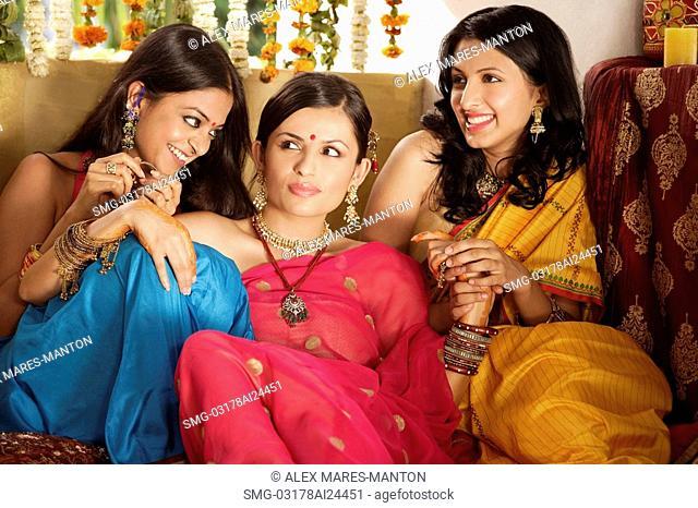 three young women wearing saris, one with bindi
