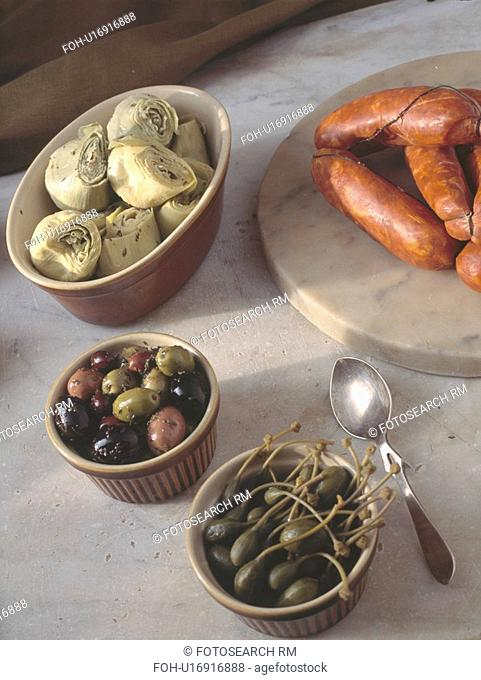 Close up of artichoke hearts and black olives in dishes