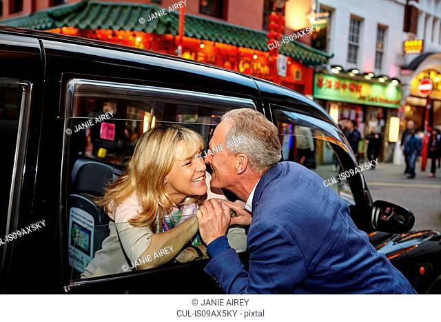 Mature dating couple kissing farewell at black cab window in China Town, London, UK