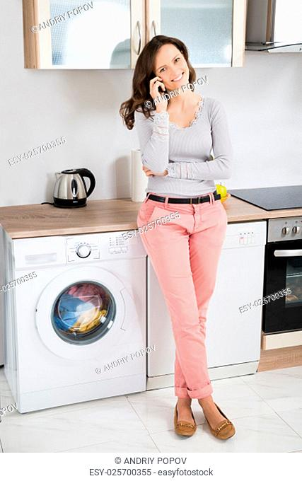Young Happy Woman Talking On Mobile Phone In Kitchen