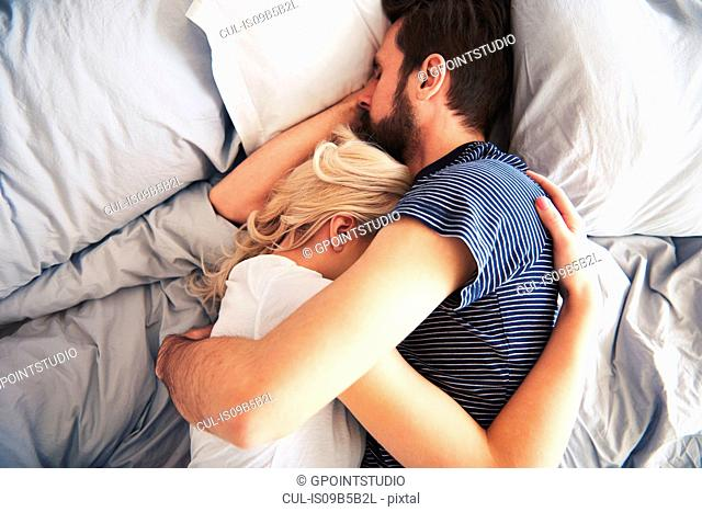 Couple lying in bed together, sleeping, arms around each other