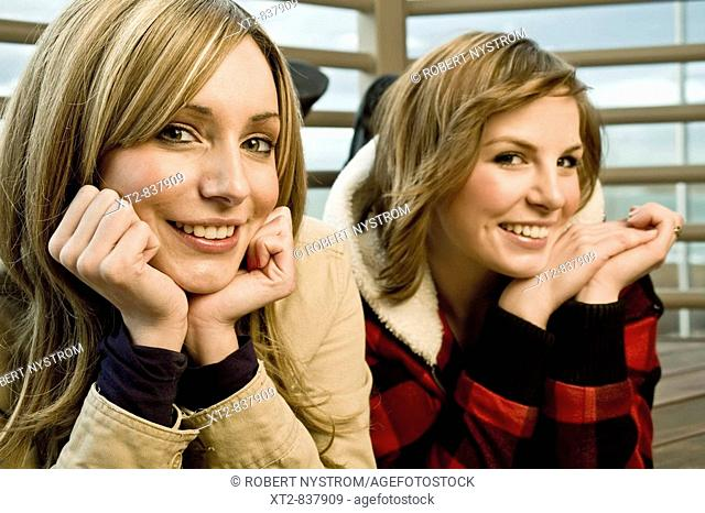 Two pretty young women rest their chins in their hands and smile for the camera