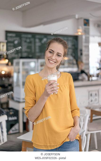 Young business owner standing in her coffee shop, drinking coffee