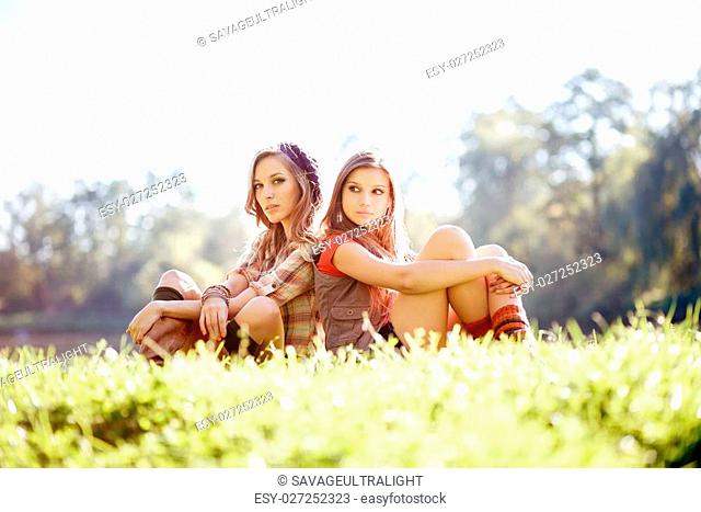 two young women sitting on grass back to back