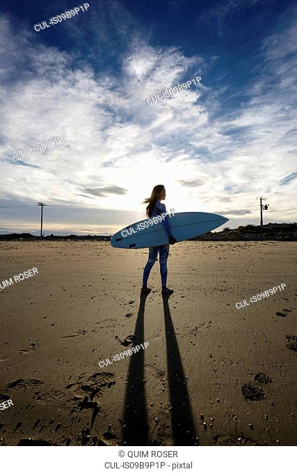 Young female surfer on beach, backlit, Tarragona, Catalonia, Spain