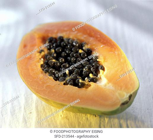 Half a papaya with seeds on a light background